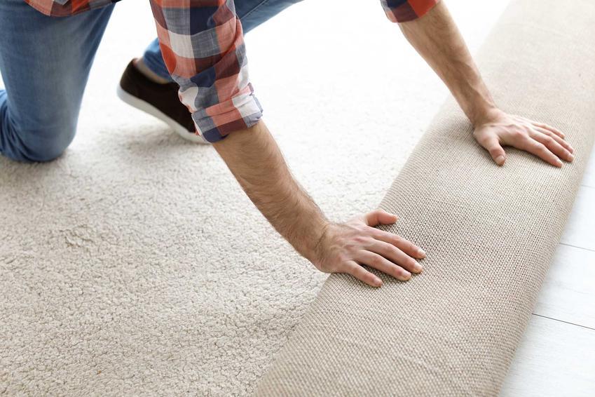 Układanie wykładziny dywanowej przez mężczyznę oraz montaż, czyli kładzenie wykładziny dywanowej krok po kroku