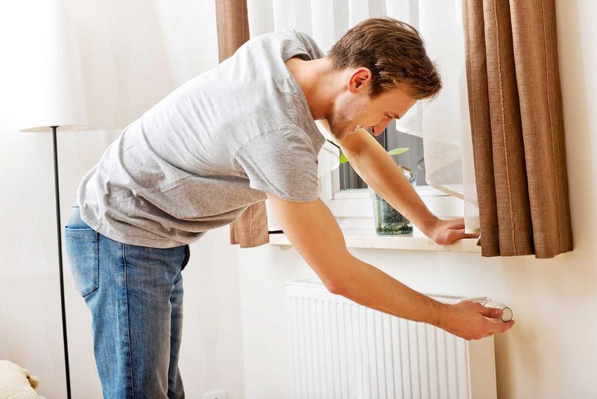 Zasada działania termostatu grzejnikowego, który reguluje młody mężczyzna oraz informacje, jak działa termostat grzejnikowy