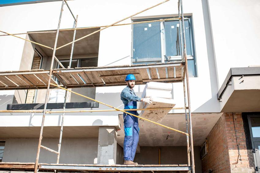Mężczyzna podczas pracy przy ocieplaniu domu oraz dofinansowanie do termomodernizacji budynku i szacowane kwoty dofinansowania