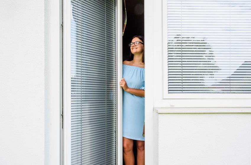 Kobieta w drzwiach balkonowych oraz ceny drzwi balkonowych i ceny okien balkonowych drewnianych i wykonanych z PCV