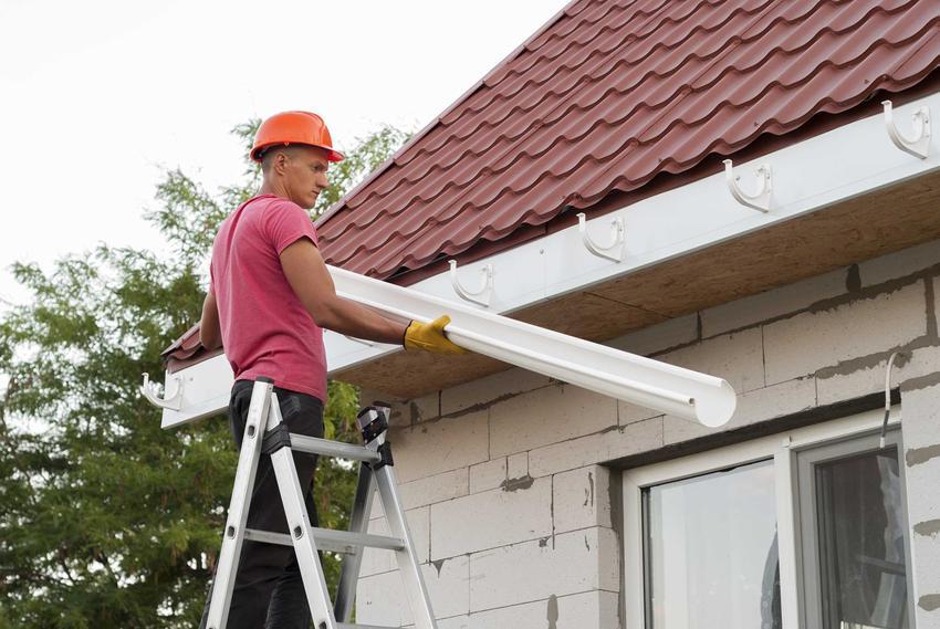 Montaż rynien przez mężczyznę oraz porady, jak montować rynny dachowe, czyli odprowadzenie wody z rynien