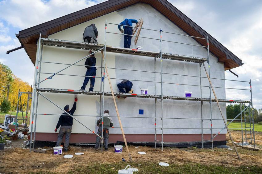 Robotnicy podczas prac oraz rusztowanie elewacyjne czy używane rusztowania fasadowe, a także wynajem rusztowań