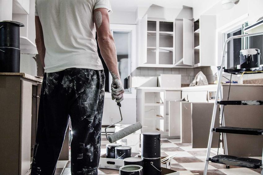 Mężczyzna podczas malowania kuchni oraz farba do kuchni i polecane zmywalne farby kuchenne - najlepsi producenci oraz zastosowanie