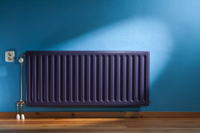 Fioletowy grzejnik na niebieskiem ścianie, czyli ogrzewanie etażowe czy też centralne ogrzewanie, jego rodzaje i koszty