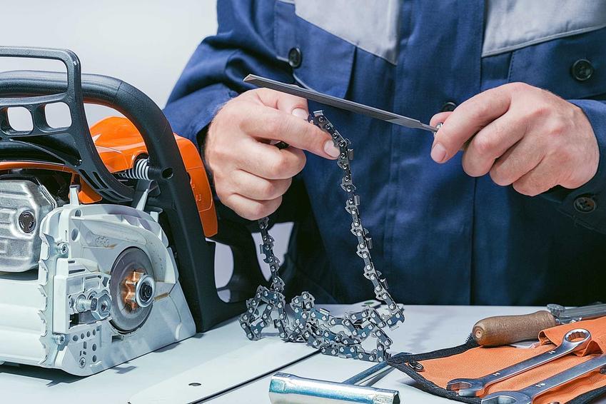 Ostrzenie łańcucha piły spalinowej przez mężczyznę oraz instrukcja, jak naostrzyć łańcuch piły spalinowej