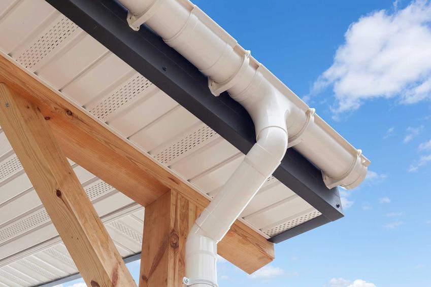 Biała rynna plastikowa zawieszona na dachu w domu jednorodzinnym, a także wszystko na temat plastikowych rynien PCV