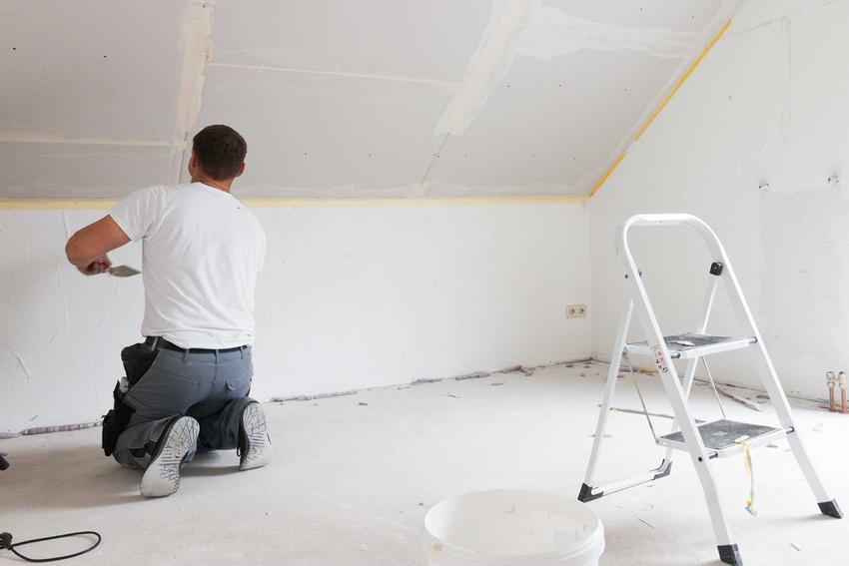 Wykończenie poddasza i mężczyzna podczas pracy, czyli adaptacja poddasza krok po kroku i przygotowanie poddasza do zamieszkania