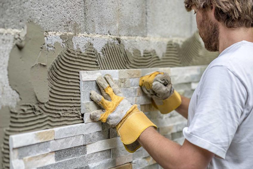 Mężczyzna podczas klejenia kamienia oraz polecany klej do kamienia naturalnego i elewacyjnego, a także rodzaje klejów i ceny