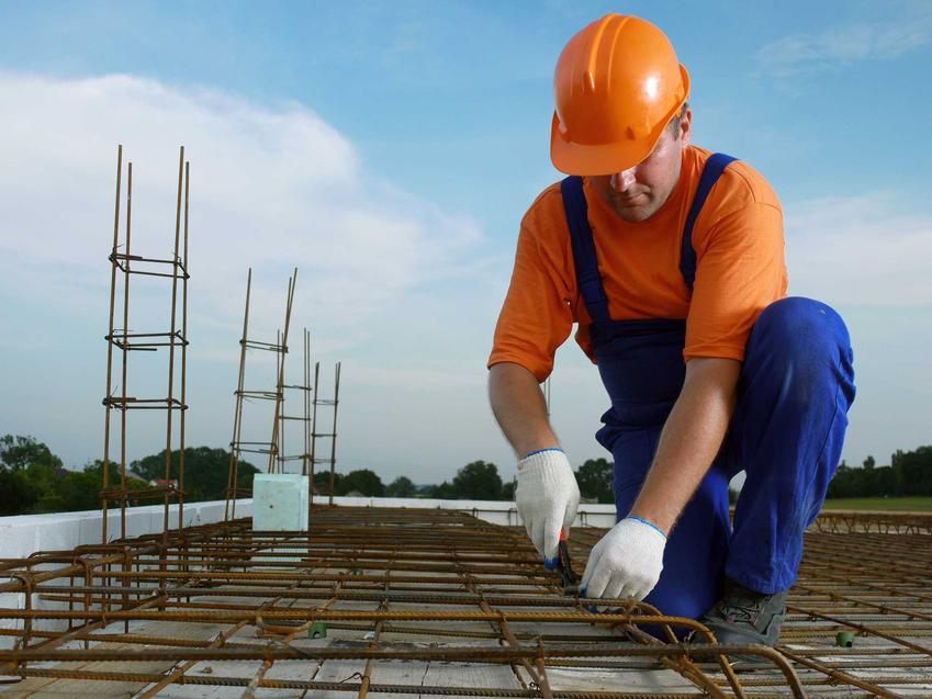 Zbrojenie stropu przez mężczyznę na budowie, czyli zsady zbrojenia stropu żelbetowego i zbrojenie płyty stropowej