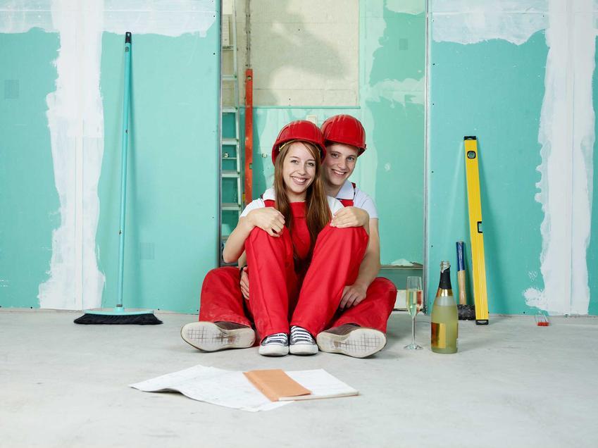 Wykończenie łazienki w nowym mieszkaniu przez parę młodych ludzi ubranych w stroje robocze, odpoczywających na podłodze w łazience na tle malowanych ścian