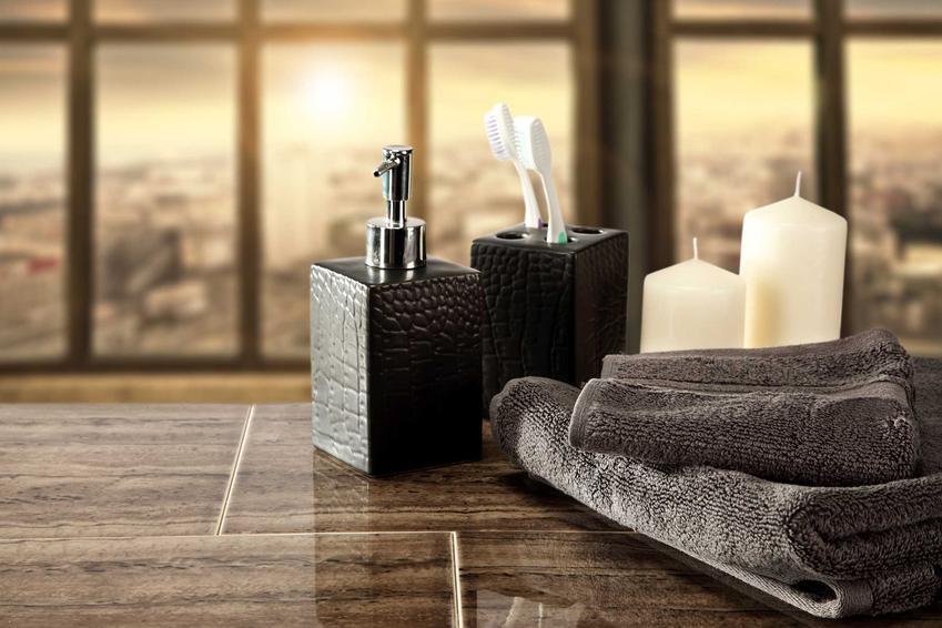 Dodatki do wykończenia łazienki: zestaw pojemników na mydło i szczoteczkę do zębów, ręczniki i świece