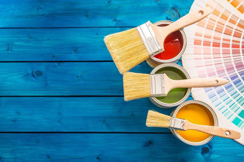 Farba akrylowa do drewna w trzech kolorach w niewielkich puszkach na derwnianym, pomalowanym na niebiesko stole obok pędzli i próbnika kolorów