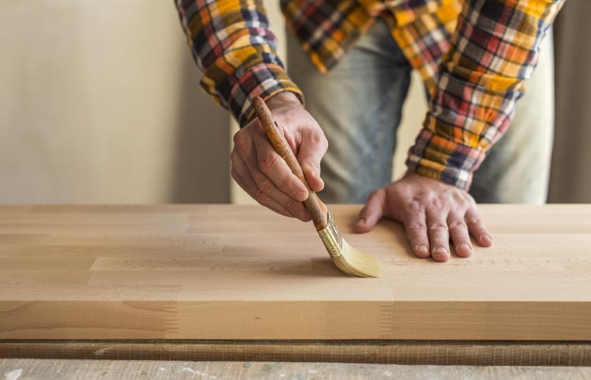 Wosk do drewna podczas stosowania przez mężczyznę oraz polecany wosk do drewna, w tym wosk pszczeli, wosk do drewna barwiący i wosk stolarski