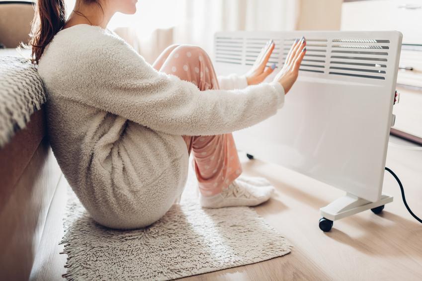 Kobieta prze elektrycznym kaloryferem, a także czyste ogrzewanie domu i znaczenie tego pojęcia