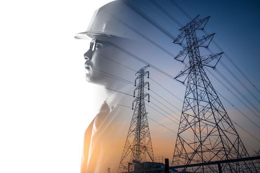 Mężczyzna na tle linii wysokiego napięcia oraz prąd budowlany i taryfa budowlana