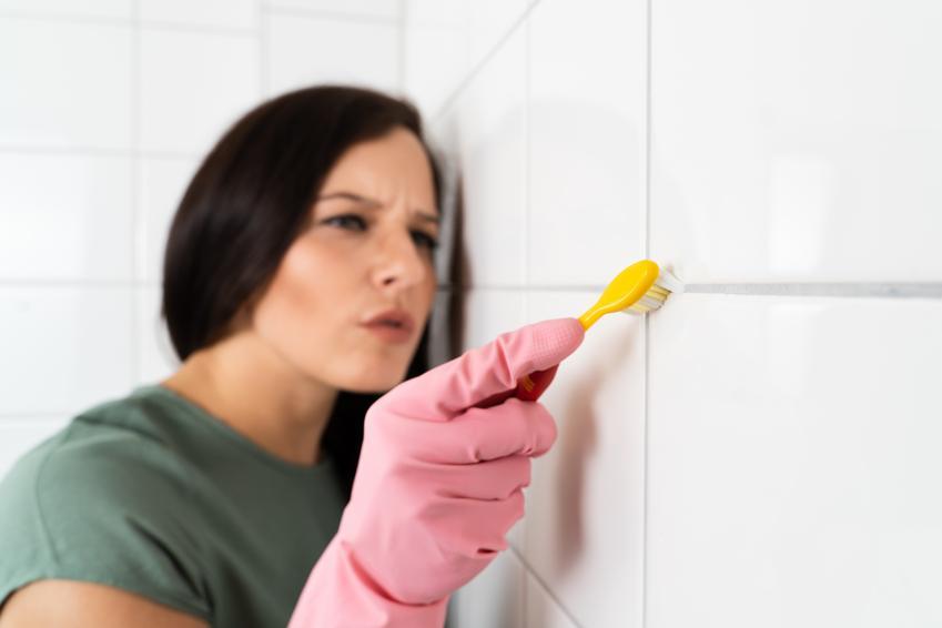 Kobieta podczas czyszczenia fug szczoteczką do zębów oraz domowe sposoby na czyszczenie fug