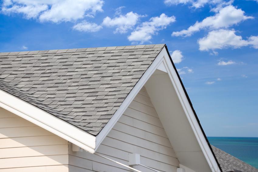 Dach na tle nieba oraz wiatrownice dachowe, na przykład wiatrownica drewniana