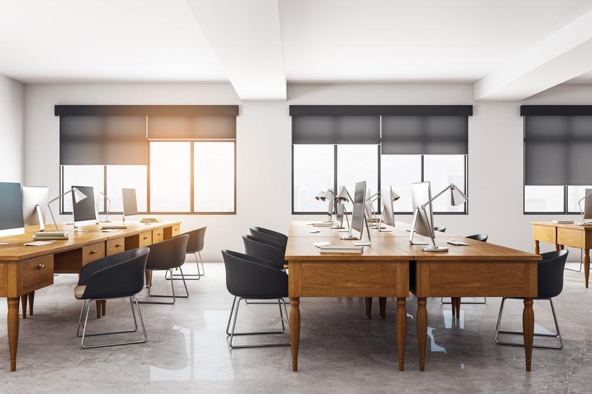 Pięknie zaaranżowany nowoczesny salon i rolety odbijające promienie słoneczne w oknach