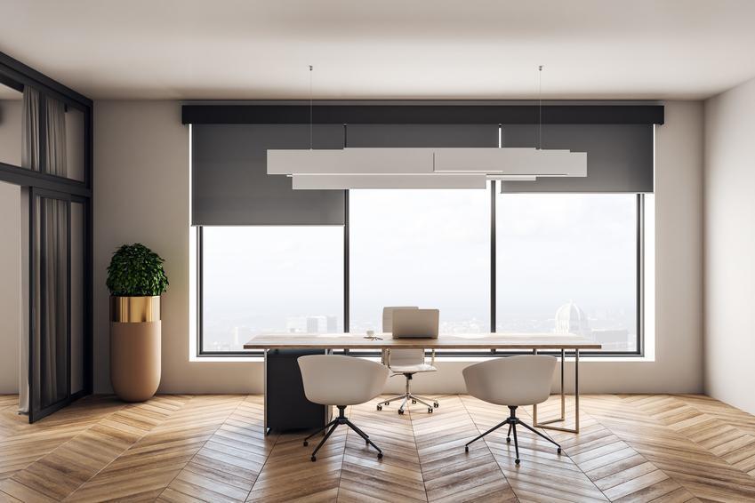 Nowoczesny salon z dużymi oknami oraz rolety odbijające promienie słoneczne i ich rodzaje