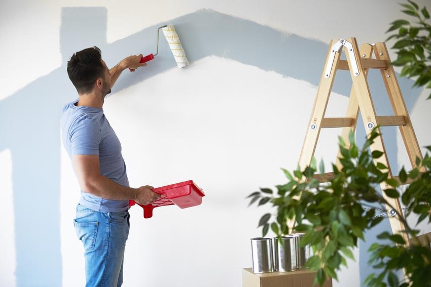Mężczyzna podczas malowania ścian, czyli najlepsza farba zmywalna do ścian i jej ceny