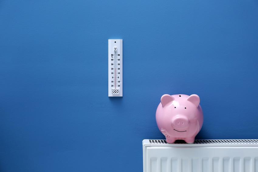 Świnka skarbonka na grzejniku i na tle niebieskiej ściany, a także koszty ogrzewania domu jednorodzinnego