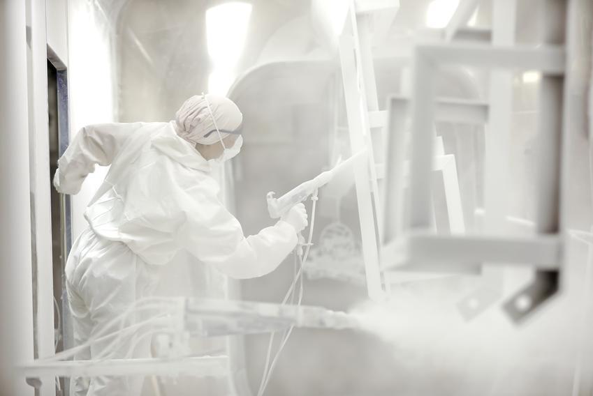 Mężczyzna podczas lakierowania proszkowego, a także lakier proszkowy i farby proszkowe
