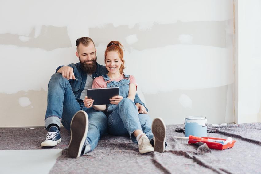 Para siedząca z tabletem w niewykończonym mieszkaniu oraz blog budowlany i forum budowlane
