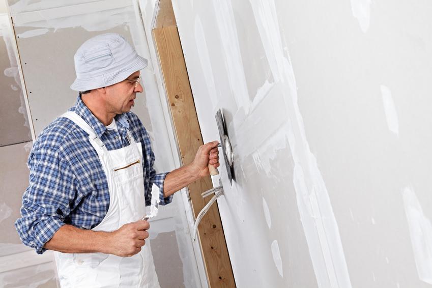 Mężczyzna podczas kładzenia gładzi na ściany, czyli porady, jak położyć gładź gipsową
