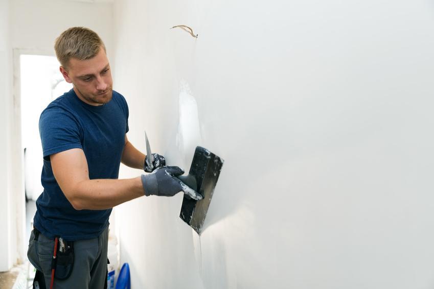 Mężczyzna podczas wyrównywania ścian, czyli porady, jak wyrównać ściany
