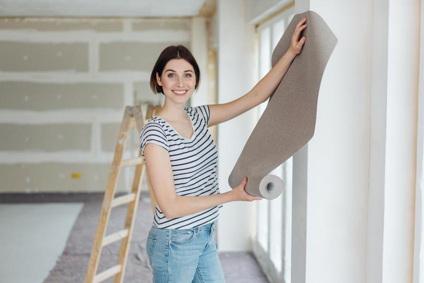Kobieta przymierzająca tapetę na ścianę, a także poradnik, jak położyć tapetę kro po kroku
