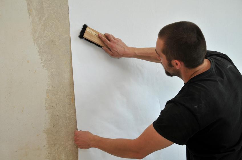 Mężczyzna przyklejający tapetę na ścianę, a także porady, jak kłaść tapetę