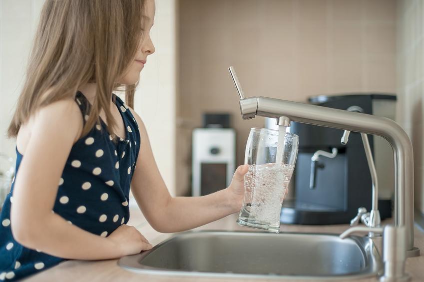 Dziewczynka nalewająca wodę z kranu, a także filtry do wody pitnej i uzdatniania wody