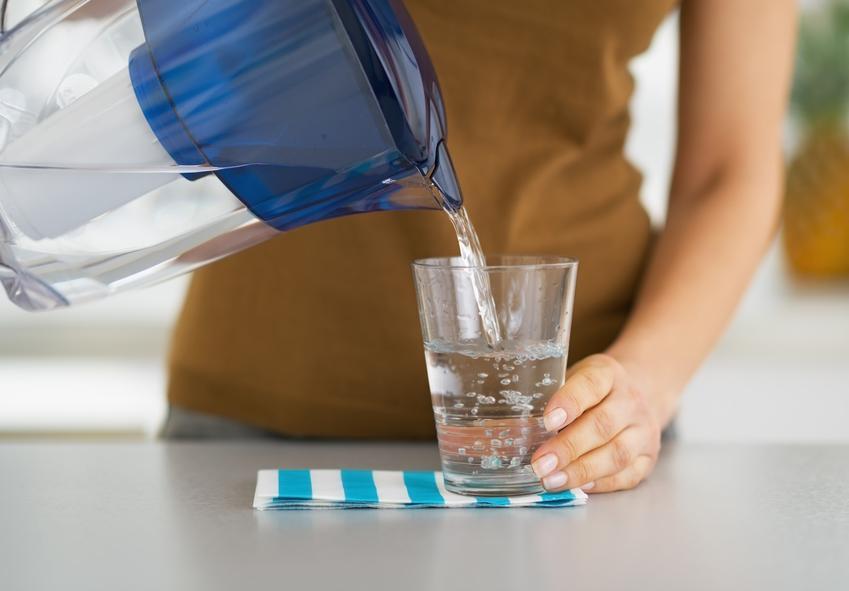 Kobieta nalewająca wodę z dzbanka z filtrem oraz polecny przepływowy filtr do wody