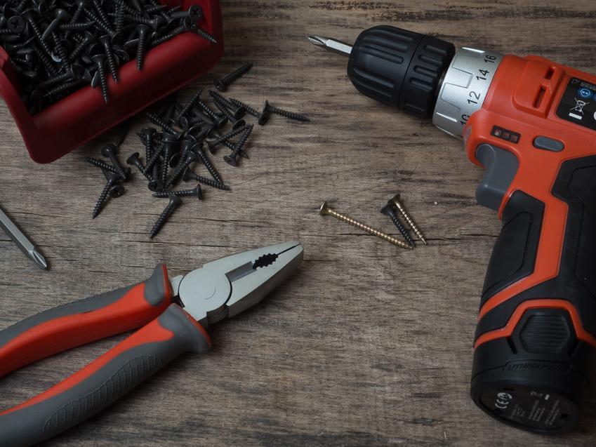 Wkrętarka leżąca z wkrętami i narzędziami na stole, a także polecana wkrętarka Hitachi