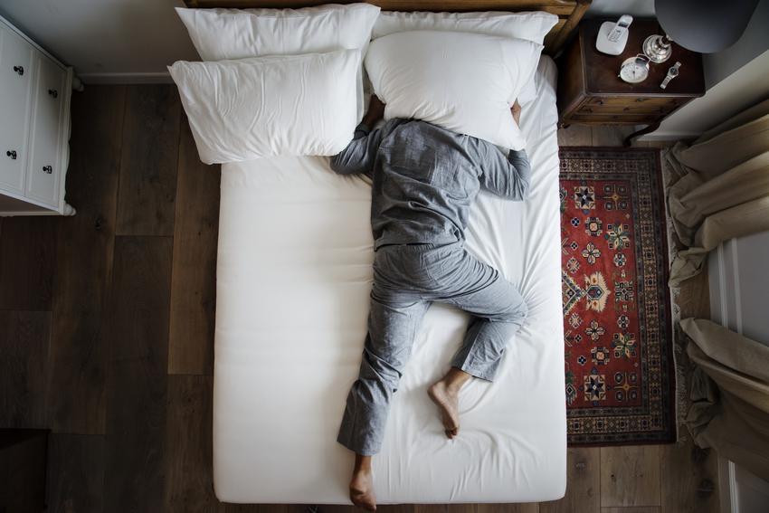 Mężczyzna z głową nakrytą poduszką, który nie może spać, czyli zakłócanie ciszy nocnej