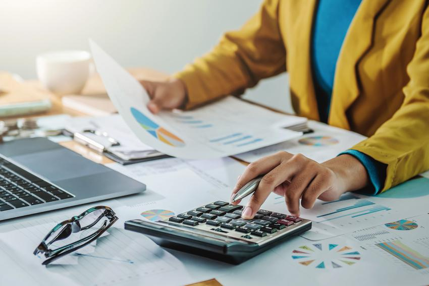 Kobieta w biurze podczas obliczeń, a także podatek katastralny na świecie i w Polsce
