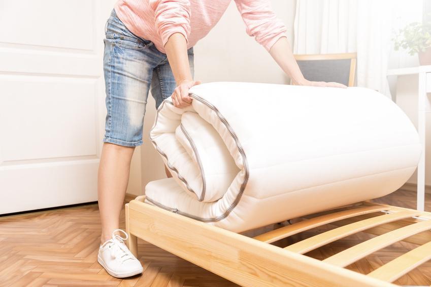 Mężczyzna rozkładający materac sprężynowy na łóżku, a także materace sprężynowe