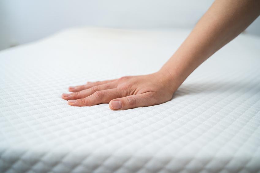 Dłoń dotykająca materac, a także materace kieszeniowe i materac sprężynowy kieszeniowy