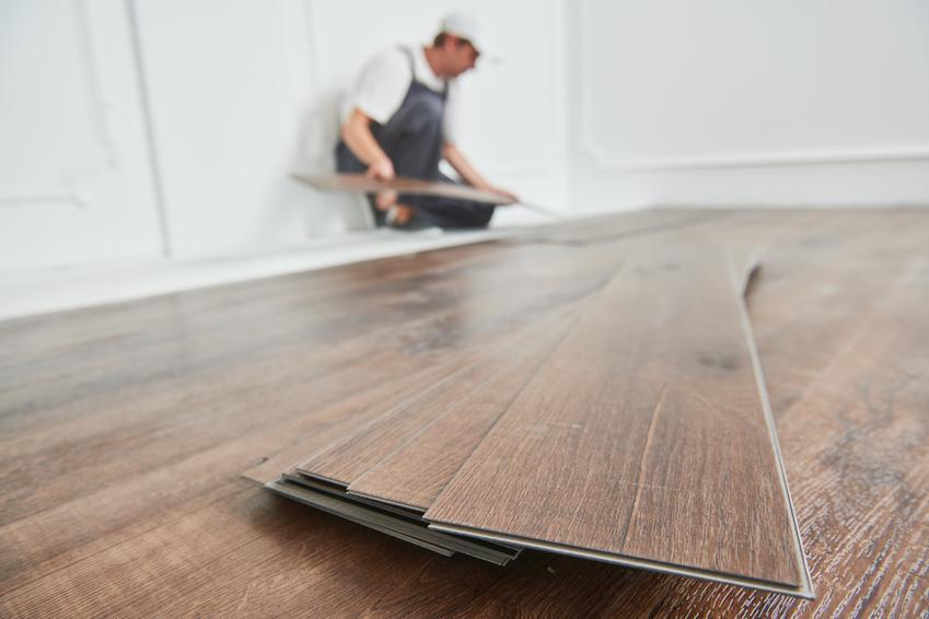 Panele podłogowe podczas układania przez mężczyznę, a także polecane rodzaje paneli, ich cechy i opinie