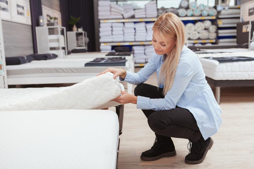Kobieta oglądająca w sklepie materac bonelowy, a także polecane materace bonelowe i ich ceny