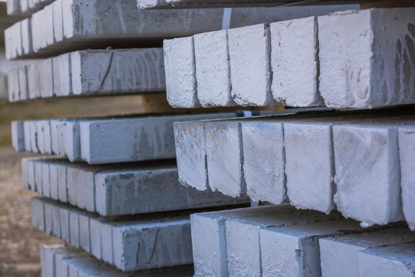 Słłupy betonowe ułożone równo na placu budowy, a także ich rodzaje i ceny
