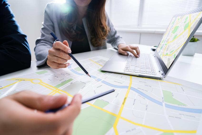 Architekci podczas dyskutowania nad projektem, a także mapa do celów projektowych i mapa zasadnicza