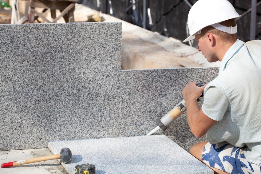 Mężczyzna podczas klejenia granitu na zewnątrz, a także polecany klej do granitu