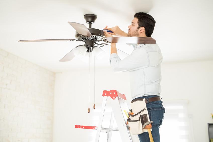 Mężczyzna montujący wentylator sufitowy, a także wiatrak sufitowy, jego rodzaje i cena