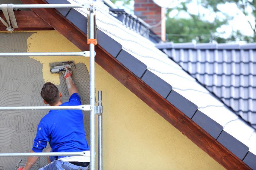 Mężczyzna podczas nakładania tynku na zewnątrz budynku, czyli tynki zewnętrzne i ich rodzaje