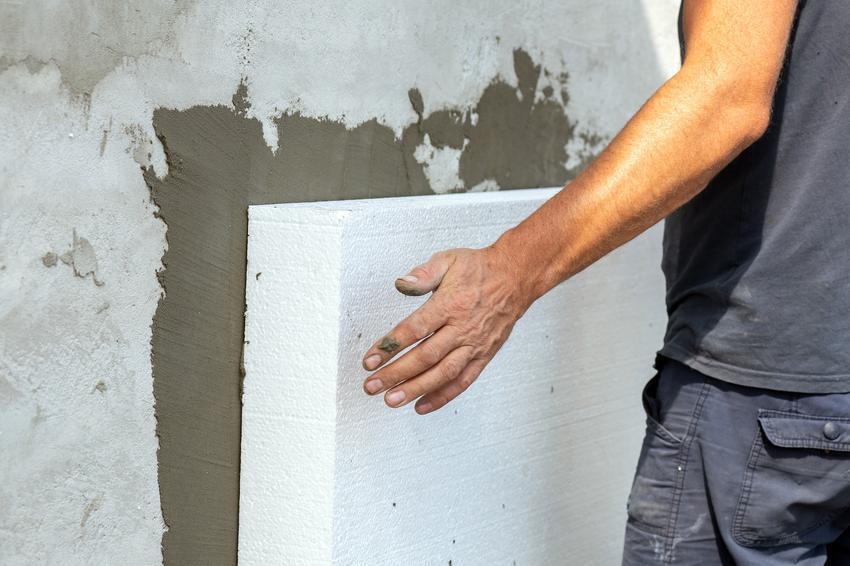 Mężczyzna podczas ocieplania domu styropianem, a także ocieplenie balkonu