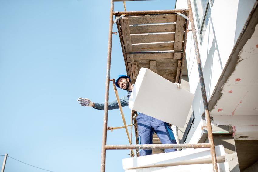 Mężczyzna na rusztowaniu podczas ocieplania domu, a także ocieplenie balkonu krok po kroku