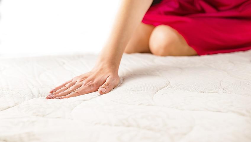 Kobieta dotykająca matarac, czyli jaki materac wybrać, materac piankowy czy sprężynowy