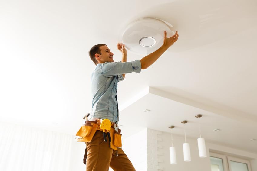Mężczyzna podczas montażu lampy sufitowej, a także lampy sufitowe LED, czyli ledowe oświetlenie sufitowe