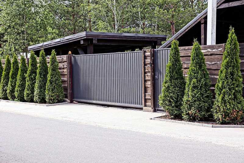Brama przesuwna w eleganckim ogrodzeniu przed domem, a także przegląd modeli, ceny i zastosowania bramy automatycznej przesuwnej